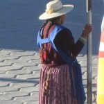 A woman wears red pom-poms in her hair, Uyuni