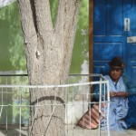 A woman sits on a doorstep in Uyuni