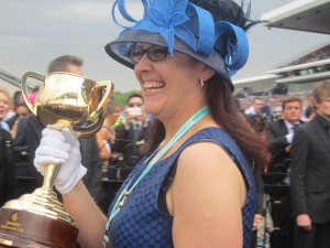 The lady happily carries the winning trophy which will be presented to the winner