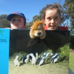 Caoimhe, Liam and Lewis the Lion peek over the penguin sign