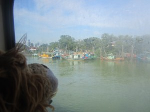 Lewis looks out of the porthole to seethe colourful boats in the Mersing harbour