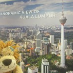 Lewis the Lion stands next to a poster of the KL skyline