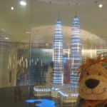 Lewis the Lion poses next to a model of the Petronas Towers