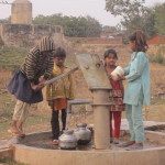 Children fill waterpots at the village well