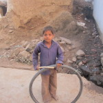 A boy plays with a tyre-inner and stick