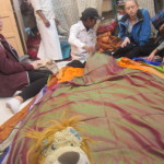 Lewis admires the silk saris being laid out before him