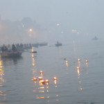 The candles and flowers float peacefully down the Ganga